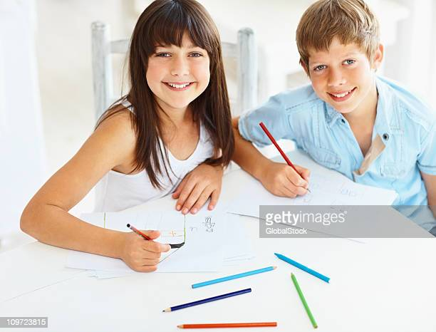 Little girl and boy drawing at school