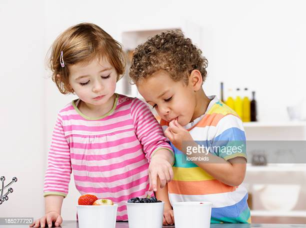 Little Girl And Boy Eating Fruit In the Kitchen