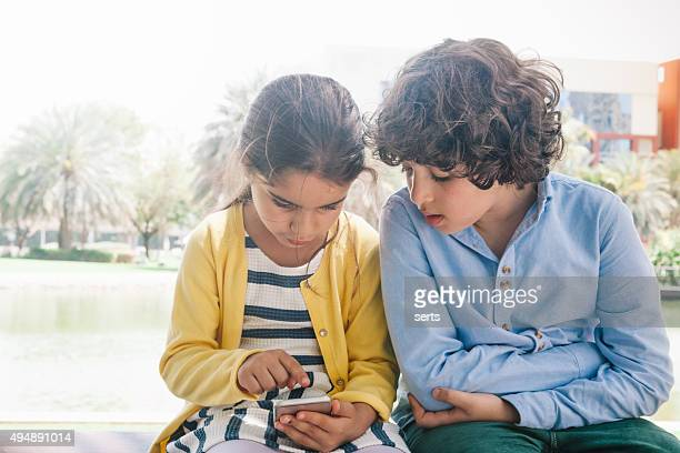Little girl and boy enjoying smartphone at park