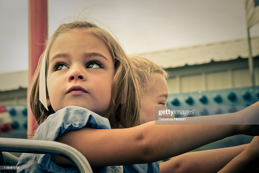 Little girl and boy on carnival ride : Stock Photo