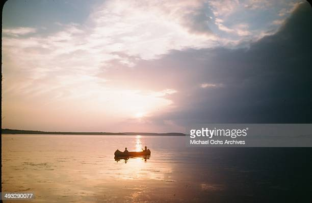 A little girl and boy paddle a canoe at sunset in July 1946 in Denmark
