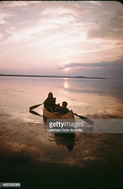 A little girl and boy paddle a canoe in Denmark in July 1946