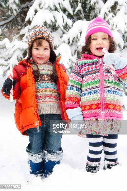 Little Girl and Boy Playing in Snow Eating Candy Canes