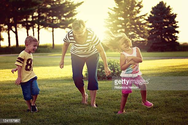 Little girl and boy playing tag with their grandma