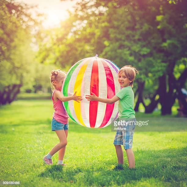 Kleines Mädchen und Jungen spielen mit Kugel