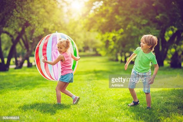 Niña pequeña y niño jugando con bola