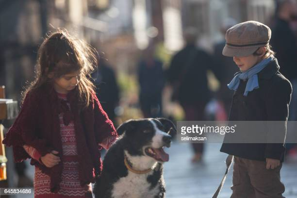 Little Girl And Boy Playing With Lovely Dog