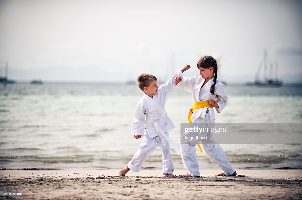 Little girl and boy practicing karate on the beach