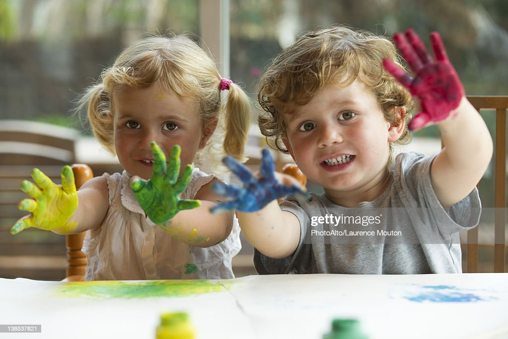 Little girl and boy showing hands covered in paint, portrait : Stock Photo