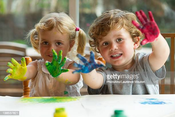 Little girl and boy showing hands covered in paint, portrait