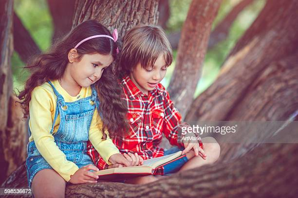 Little girl and boy with book in autumn