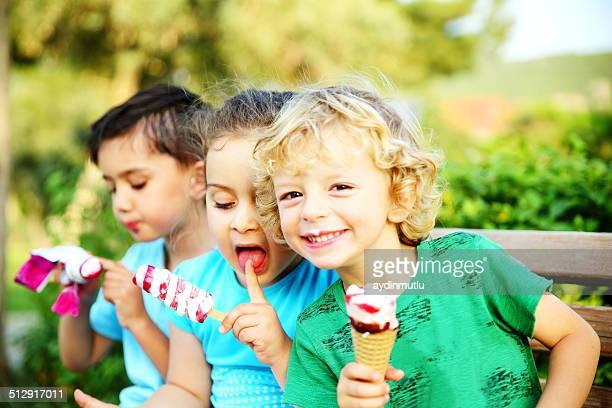 Kleine Mädchen und Jungen Essen Eis im park.