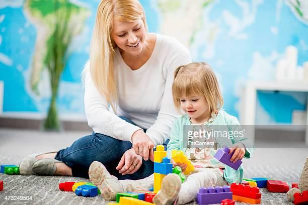 Kleines Mädchen und Pflege Freude. in Kindertagesstätten