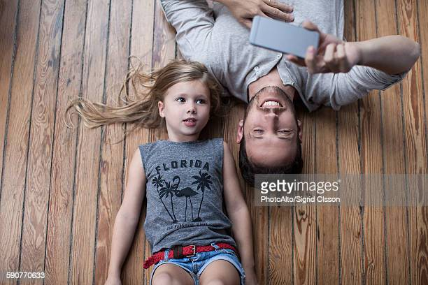 Little girl and father lying on floor together looking at smartphone