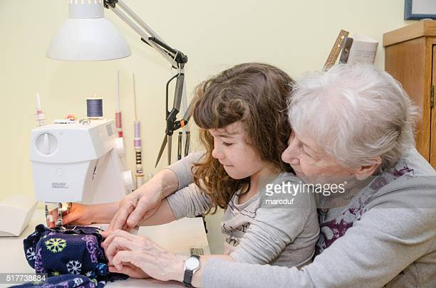 Little girl and grandmother on sewing machine