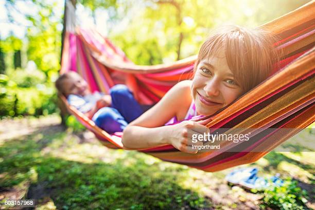 Little girl and her brother playing on hammock