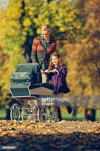 Little girl and her mother pushing a baby carriage in autumnal park