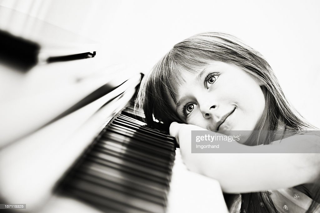Little girl and her piano : Stock Photo