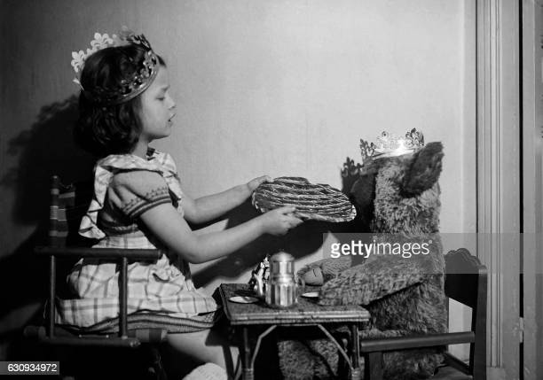 A little girl and her teddy bear eat a king cake to celebrate Epiphany in the 50's in Paris / AFP /