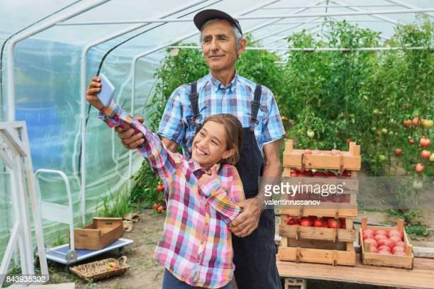 Petite fille et agriculteur mature prenant selfie dans le jardin