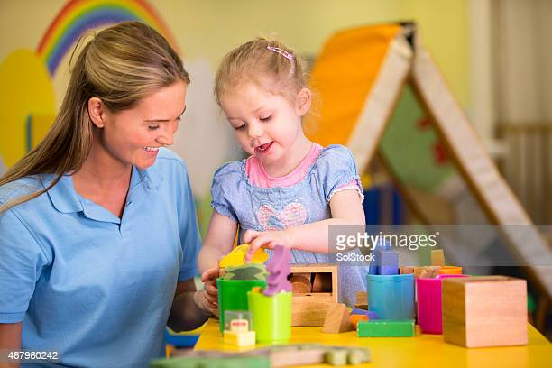 Little girl and nursery teacher playing with building blocks