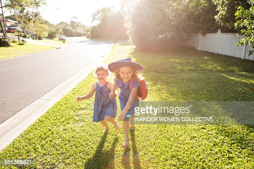 Little girl and sister walking to school Australia