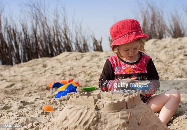 Little girl at the beach building a sandcastle