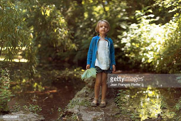 Little girl at the water's edge with tree leaf