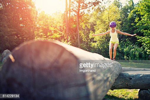 Little girl balancing on a trunk in adventure park