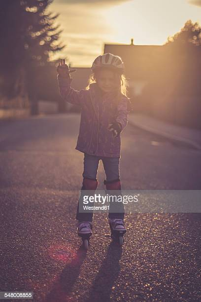 Little girl balancing on rollerblades at backlight