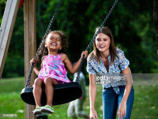 Little girl being pushed on a swing smiling
