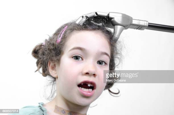Little girl being surprised while a robot hand scratches her head