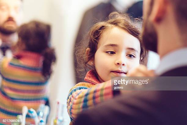 little girl binding tie to father in business outfit