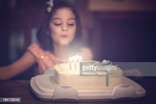 little girl blowin out birthday candles : Stock Photo