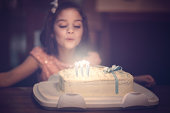 little girl blowin out birthday candles
