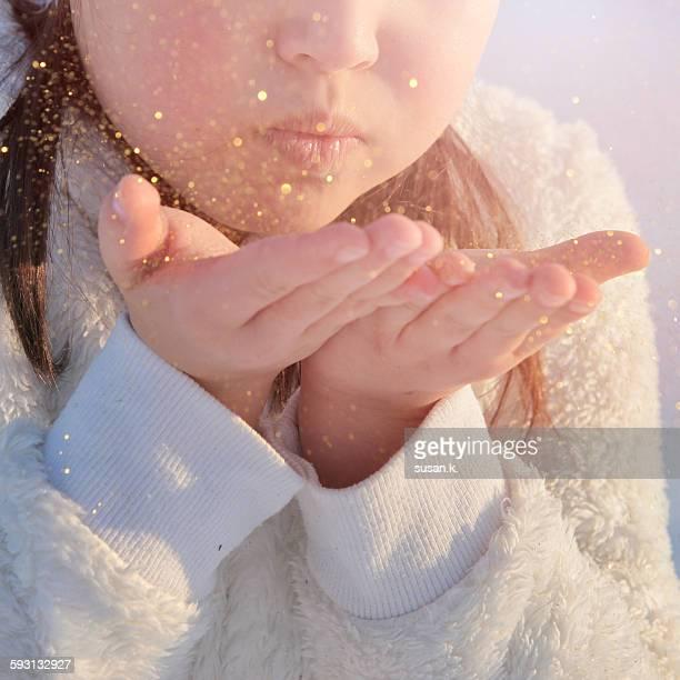 Little girl blowing golden dust