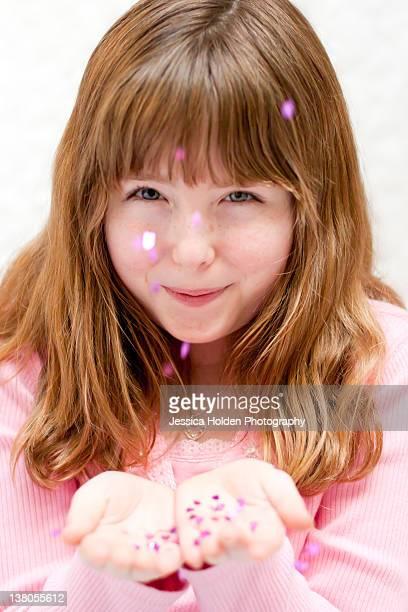 Little girl blowing heart confetti