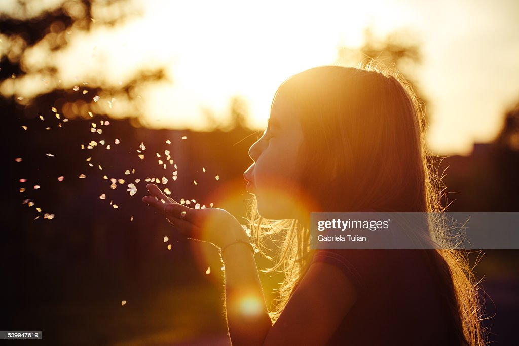 Little girl blowing hearts in the sunset