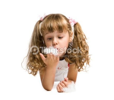 little girl blowing on a feather : Stock Photo