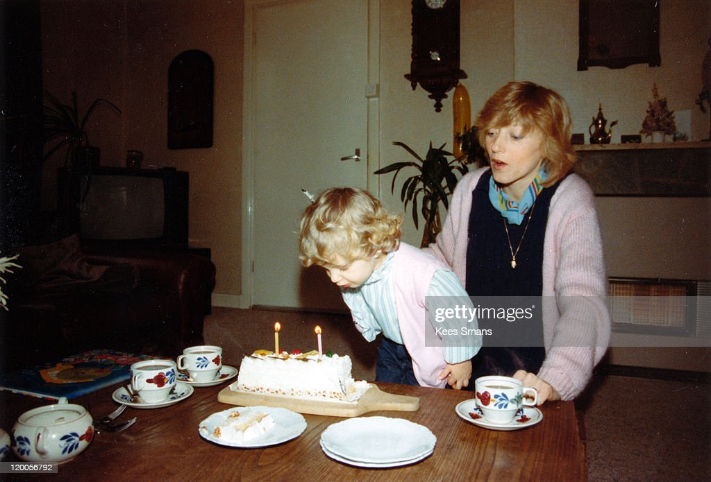 Little girl blowing out birthday candles : Stock Photo