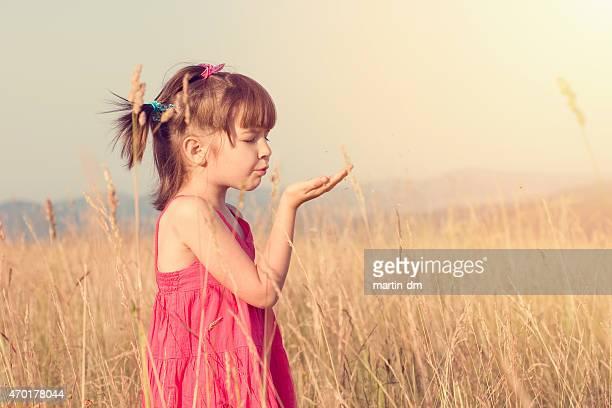 小さな女の子は彼女のヤシから吹く種子