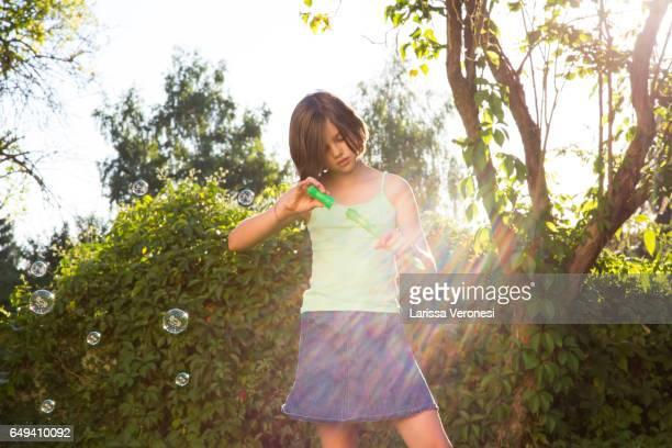 Little girl blowing soap bubbles on a meadow
