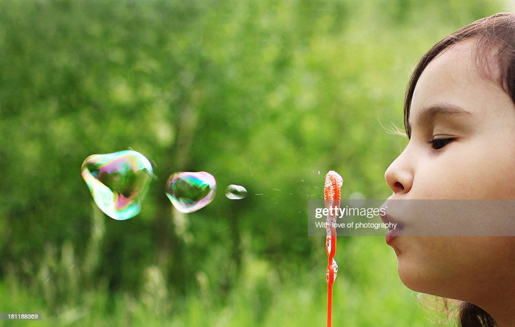 Little girl blowing water bubbles
