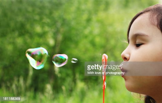 Little girl blowing water bubbles