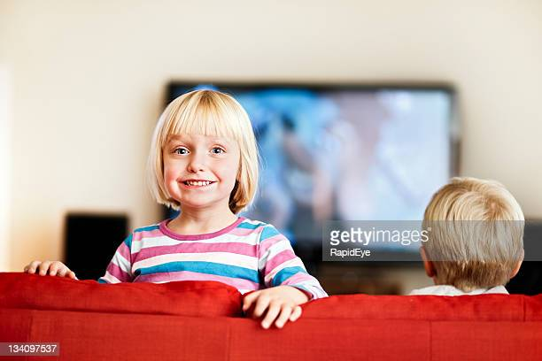 Little girl bounces up from couch to smile at camera.