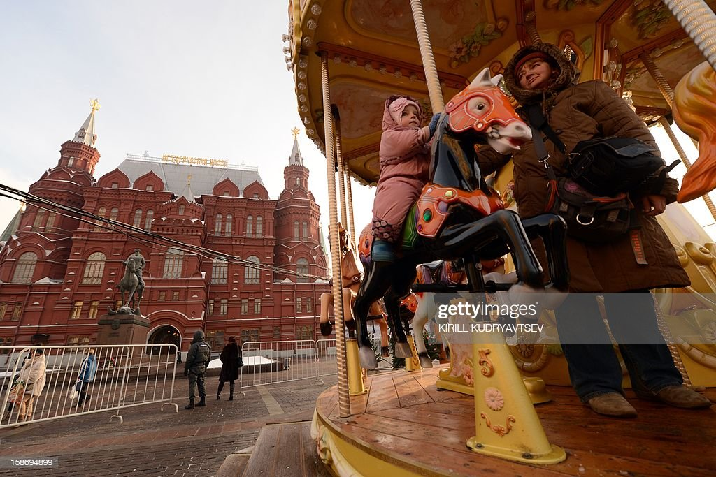 A little girl braves the freezing outdoors while riding a horse on the merry-go-round at the site of the First Christmas fair from Strasbourg just outside the Kremlin in Moscow, on December 24, 2012. The temperatures in Moscow dropped today to -22C (-7F), but due to high humidity and strong cold wind, weather experts said it would feel more like -26C (-14F).