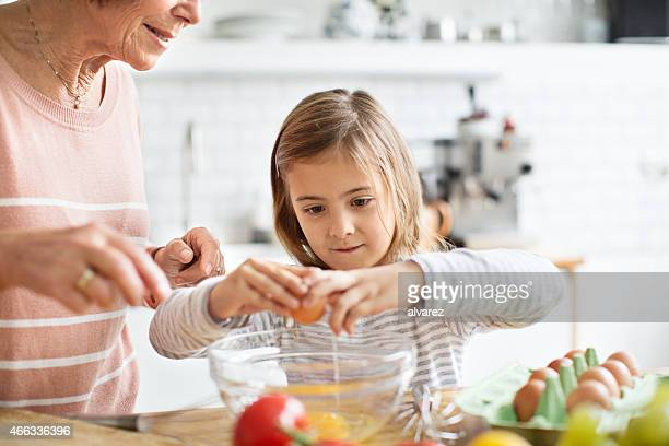 Little girl breaking an egg in kitchen