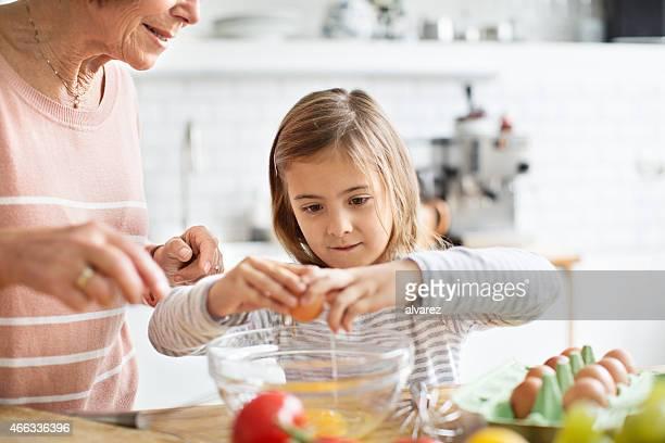 Petite fille se briser un œuf en cuisine
