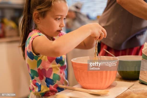 little girl breaking eggs