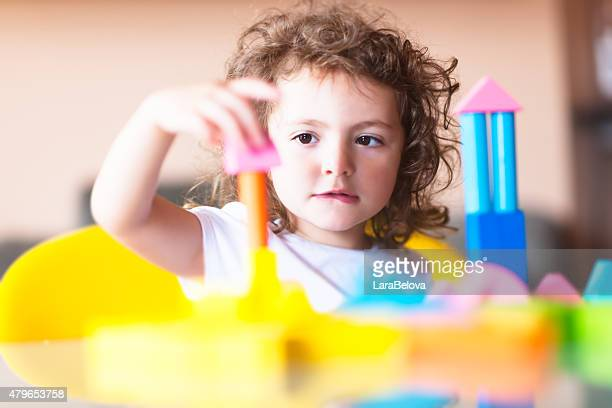 Little girl building a house with cubes